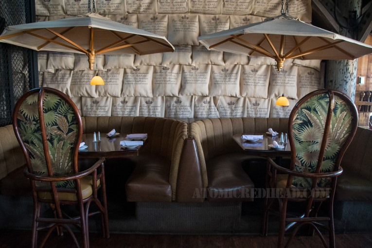 Inside: Two half circle booths of tan upholstery, cream patio umbrellas hang, on the wall rows of canvas bags hang.