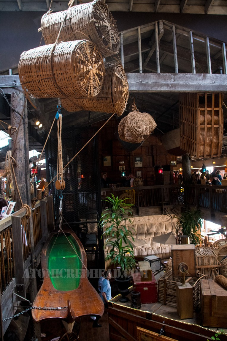 A view from the upstairs, overlooking large wooden crates, wicker barrels hang from above. A canoe hangs along the left.