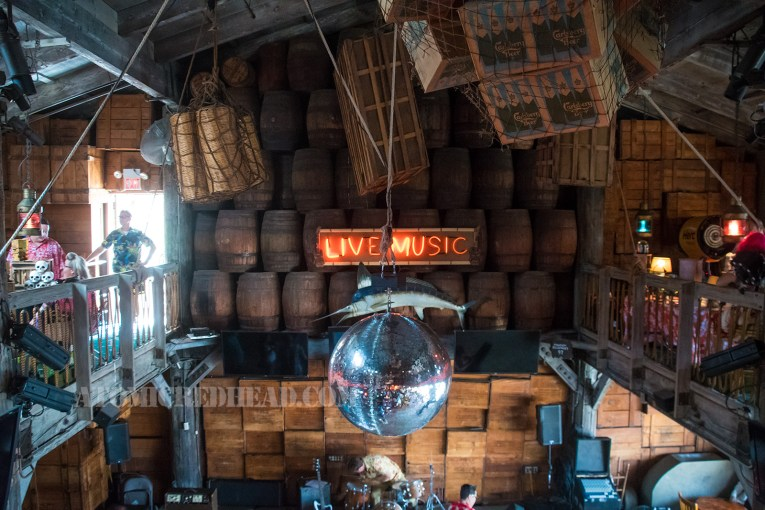 "A view from above, wooden barrels line the wall, with neon reading ""Live Music"" and below that a large blue marlin hangs. In the center a massive disco ball. Also hanging from the ceiling are multiple boxes, some in large nets."