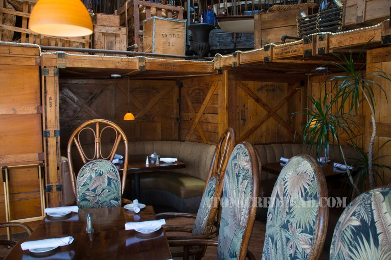 Large shipping crates now create intimate half circle booths, upholstered in a tan fabric. A large table is in the foreground, with massive bamboo chairs with leafy upholstery of green.