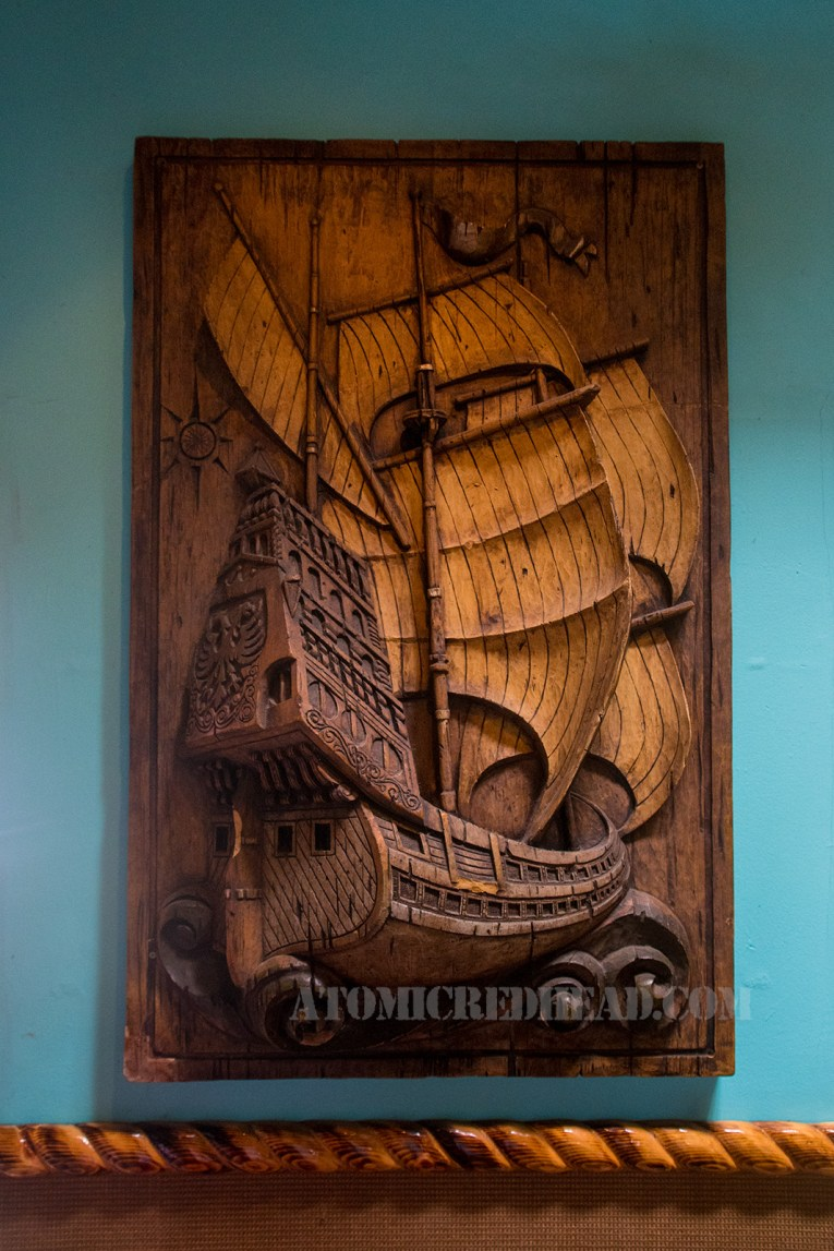 A large craved piece of wood features a massive sailing ship.
