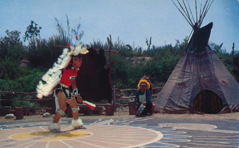 An Indian dancer with a large feather headdress dancing in the circle, a tipi sits off to the right.