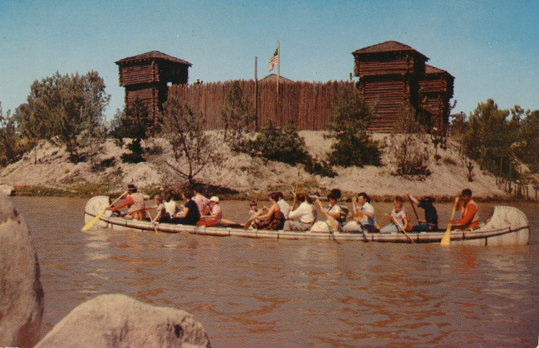 Guests paddle a canoe through the Rivers of America with Fort Wilderness in the background.