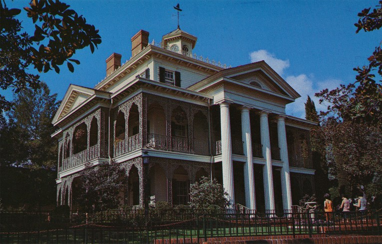 The exterior of the Haunted Mansion, done in southern plantation style, green wrought iron arches on the first and second floor with tall columns in the center.