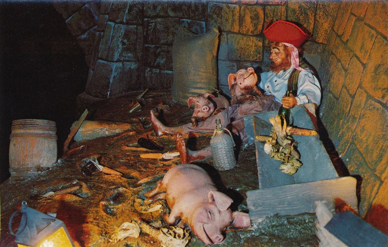Inside Pirates - a pirate sleeps in the mud with pigs, a bottle in his hand.