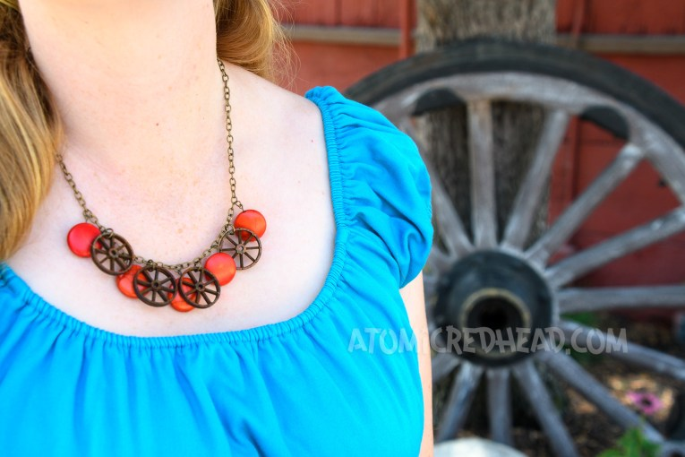 Close-up of my necklace, which features miniature wooden wagon wheels and circular faux coral stones.