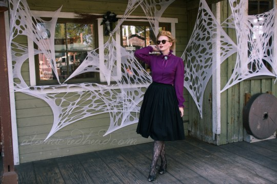 A pale green wooden building, covered in fake cob webs, myself standing in front, wearing a long sleeve purple, Victorian style shirt, with a black and white cameo, and a black full skirt, net style tights with a floral design and black shoes. My hair is piled atop my head in a Gibson Girl style.