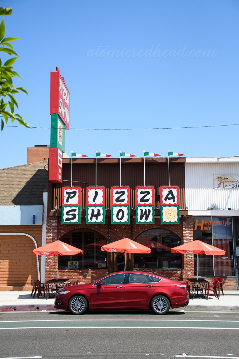 """Exterior of Pizza Show. Squares spell out """"Pizza Show"""" with """"Pizza"""" edged in red, and """"Show"""" edged in green."""