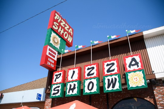 "Exterior of Pizza Show. Squares spell out ""Pizza Show"" with ""Pizza"" edged in red, and ""Show"" edged in green. A tall sign to the left also reads ""Pizza Show"" with a small sun image below. Below the sun it reads ""Dining Room Food to Go"""