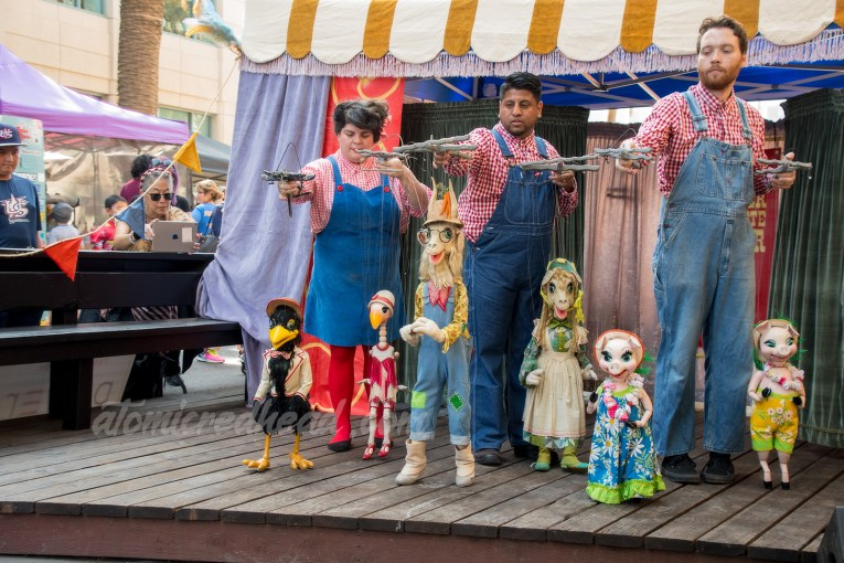 The Bob Baker Marionette performers hold puppets, including a crow, goose, two goats, and two pigs, each of which are wearing clothing.