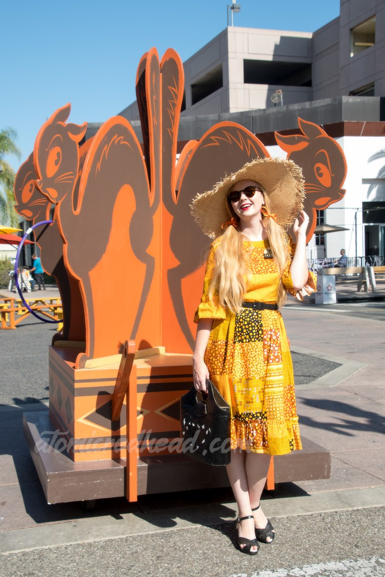 Myself standing in front of a quartette of black cats of wood, wearing a patchwork print dress of orange, yellow, black and white, as a large straw hat