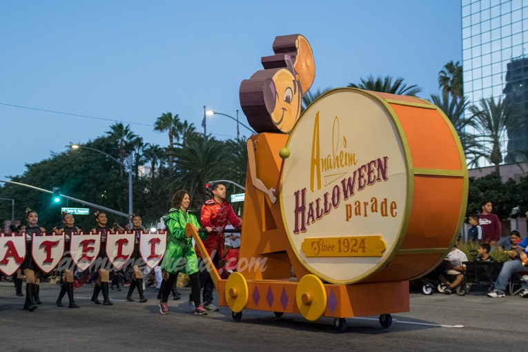 "Andy of Anaheim, the chipmunk-esque mascot of Anaheim bangs a drum reading ""Anaheim Halloween Parade Since 1924"""