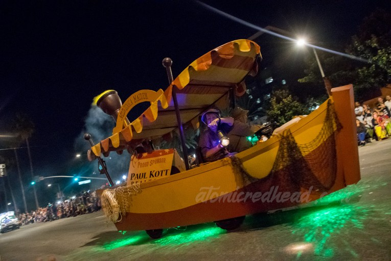 A float of a cartoon Jungle Cruise style boat, with orange and yellow stripe canopy.