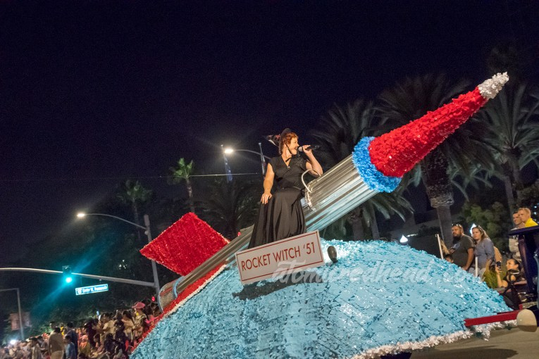 "A large silver and red rocket float with the ""Rocket Witch"" sitting atop, wearing a black dress and black witch hat."