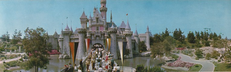 Sleeping Beauty's Castle, with a large moat around it, and people crossing the drawbridge.