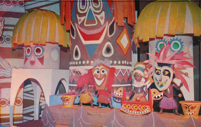 Inside it's a small world: New Guinea children play drums and wear masks with large totems behind them.
