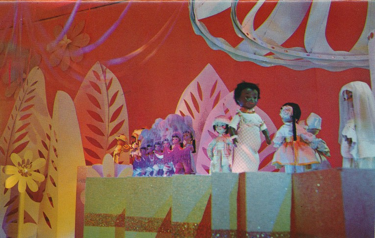 Inside it's a small world: finale scene where every child wears white, but still in traditional garb. African children dance, with girls doing the can-can in the distance.