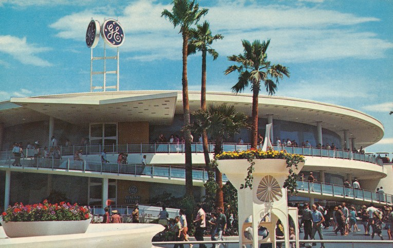 """The white circular building for the Carousel of Progress, a tall """"GE"""" sign atop."""