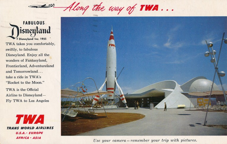"""A towering white rocket with red stripes. Photograph is edged in white with text reading """"Along the way of TWA... Fabulous Disneyland. TWA takes you comfortably, swiftly, to fabulous Disneyland. Enjoy the wonders of Fantasyland, Frontierland, Adventuerland, and Tomorrowland...take a ride in TWA's 'Rocket to the Moon.' TWA is the Official Airline to Disneyland - Fly TWA to Los Angeles. TWA Trans World Airlines USA - Europe - Africa - Asia. Use your camera - remember your trip with pictures."""