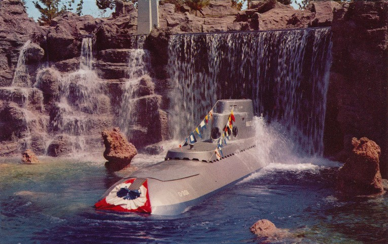 A grey submarine emerges from a waterfall.