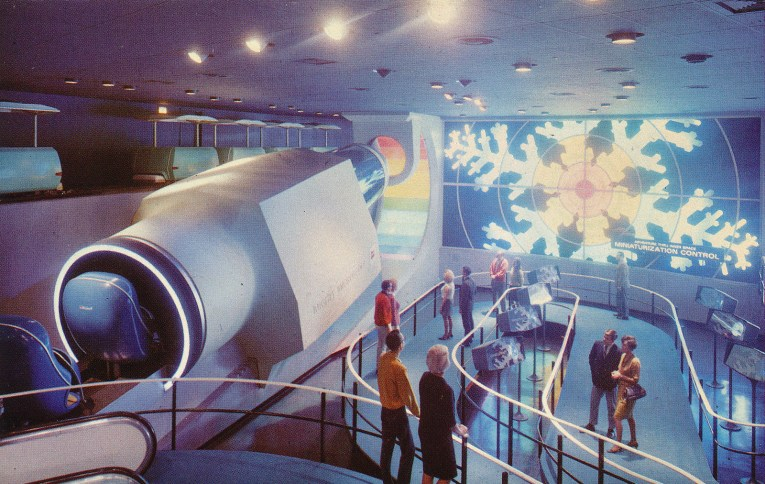 "A large ""shrinking"" machine stands on the left, as guests walk through the area on the right. A large screen of a snowflake on the back wall."