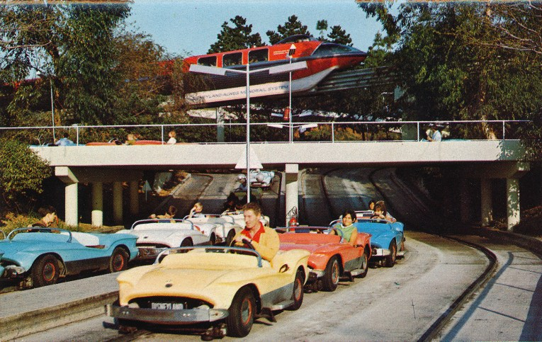 Autopia cars now on guide rails down the center of the track. The Monorail moves in the distance.
