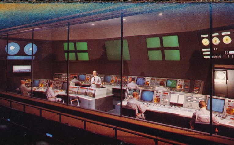 Mission Control for Rocket to the Moon. Men sit at large computer consoles, large screens make up parts of the walls.