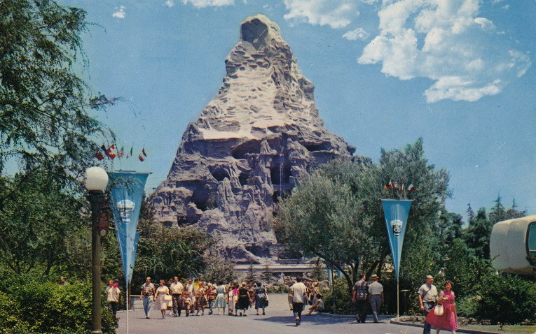 Guests walk toward the tall Matterhorn, white with snow on top.