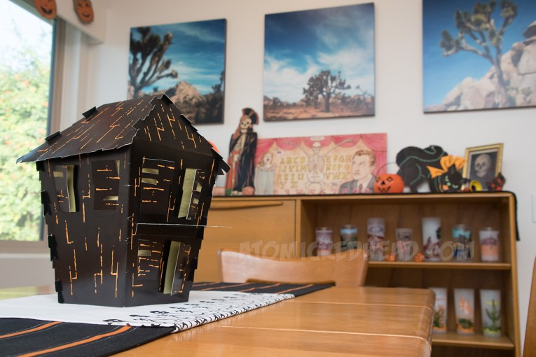 A cardboard haunted house, with shutters that are open, revealing yellow tissue paper behind them.