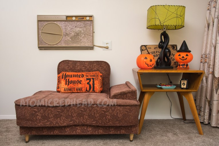 An upholstered 50s chair on the left, a table to the left with a black lamp with green lamp shade, below it, a plastic jackolantern trick or treat bucket, and a plastic pumpkin with a witch hat.