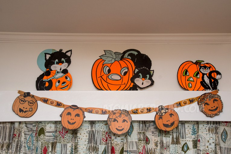 Above a window, three black cats with pumpkins, hanging below them a series of jackolanterns with funny faces and hats.