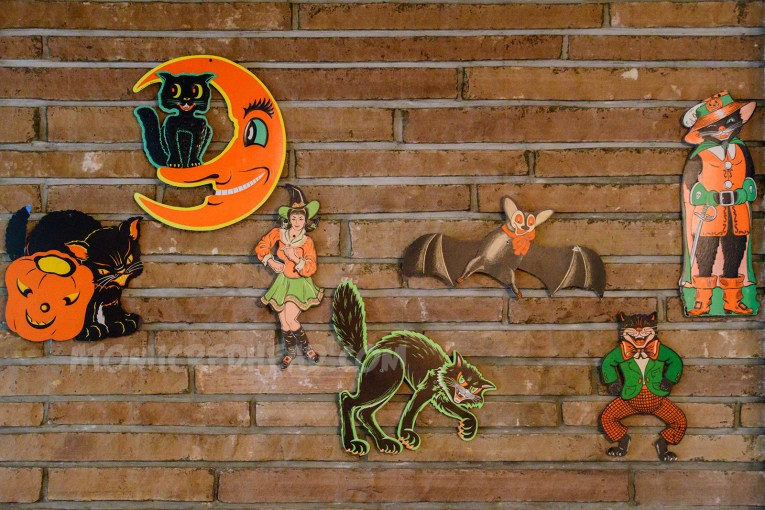 Hanging from the fireplace, a black cat with a pumpkin, a black cat sitting in a crescent moon, a youthful witch in an orange top and green skirt appears to be dancing, a bat, a black cat in a green jacket and orange pants, and another black cat dressed as a pirate.