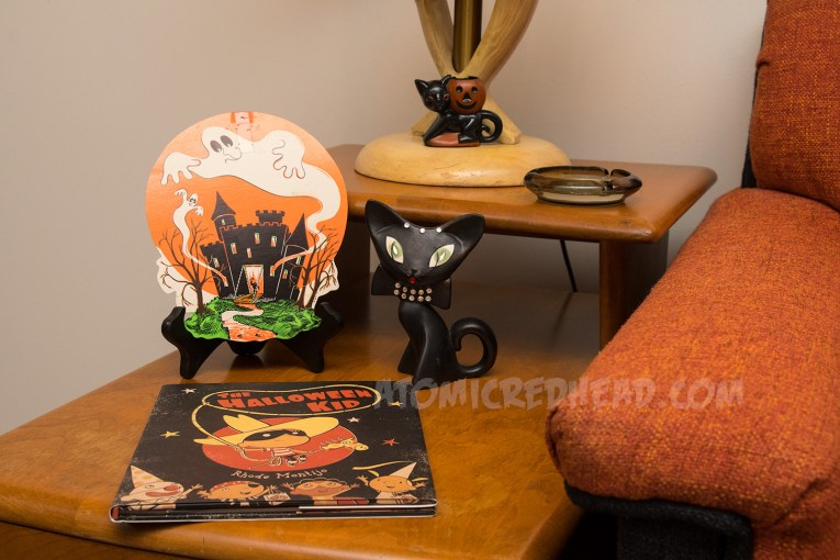 A cardboard image of a castle with a ghost emerging from it. A ceramic black cat with jewel eyes sits next to ti.