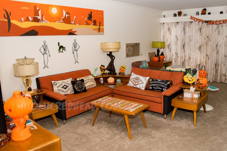 The living room decked out for Halloween with pumpkins, cats, and skeletons.