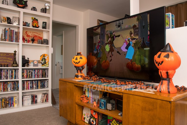 On the TV Ichabod and Katrina dance in Disney's Sleepy Hollow. Next to the TV a plastic pumpkin sitting upon a black cat on one side, on the other a plastic pumpkin atop hay with a witch's hat.