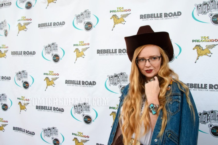 "Myself, standing in front of a backdrop featuring the Palomino logo of a horse, and text for the event company, Rebelle Road, and the museum Valley Relics, wearing a blue jean jacket, white t-shirt reading ""Gram Parsons and the Fallen Angels"" and a dark brown cowboy hat."