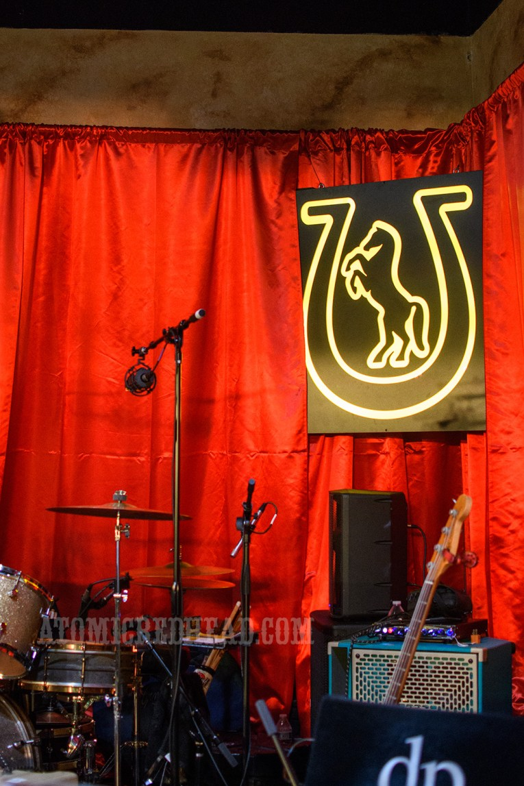 The stage, draped in red fabric. A recreation a portion of the sign that once stood outside hangs in the background, a horse rearing inside of a horseshoe.