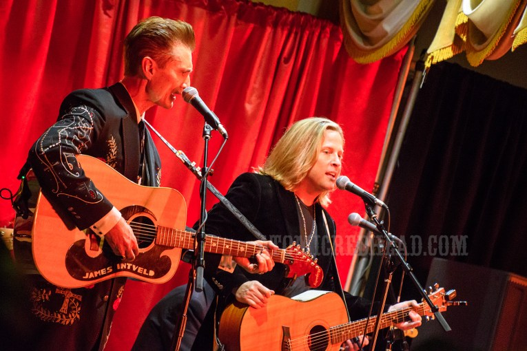 Jim Intveld performs with Rick Nelson's son, Gunnar Nelson. Both men wear black, and hold guitars.