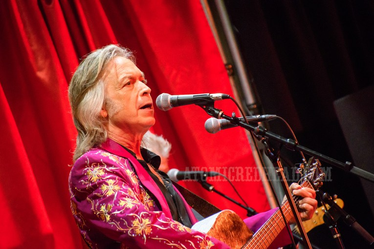 Jim Lauderdale performs while wearing a magenta suit with gold embroidered flowers akin to crosses, rhinestones dot the suit.