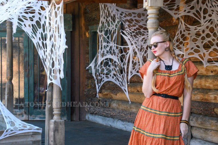 Leaning against a post, with old west buildings in the background, some of which have been covered in faux spider webs, wearing an orange dress with a small yellow and green floral print, and yellow and green rick-rack along the neckline and skirt, also wearing black tooled leather shoes, and a plastic black cat necklace.