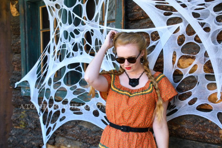 Sanding with old west buildings in the background, some of which have been covered in faux spider webs, wearing an orange dress with a small yellow and green floral print, and yellow and green rick-rack along the neckline and skirt, also wearing black tooled leather shoes, and a plastic black cat necklace.