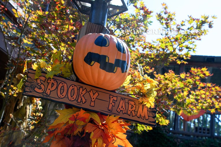 """A cartoon pumpkin with a painted on jack-o-lantern face hangs on a post, a sign reading """"Spooky Farm"""" hangs below."""