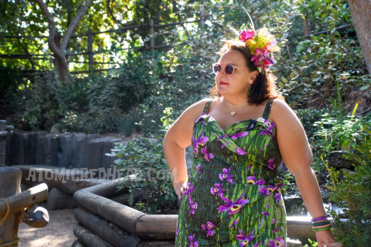 Dor, wearing a green and purple wiggle dress, featuring purple orchids. A magenta and purple orchid flower crown with green leaves jutting from it sits atop her head.