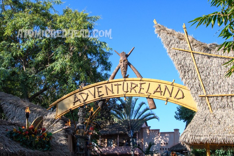 """The entrance to Adventureland, featuring thatch roofs on either side, an arch of reed and bamboo reading """"Adventureland"""" across it. A tiki mask above the arch."""