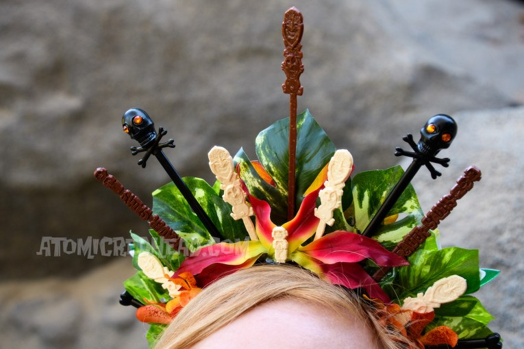 Close up of my flower crown, orange and white flowers, backed with green leaves, various swizzle sticks, including tikis, and skulls, jut from the top.