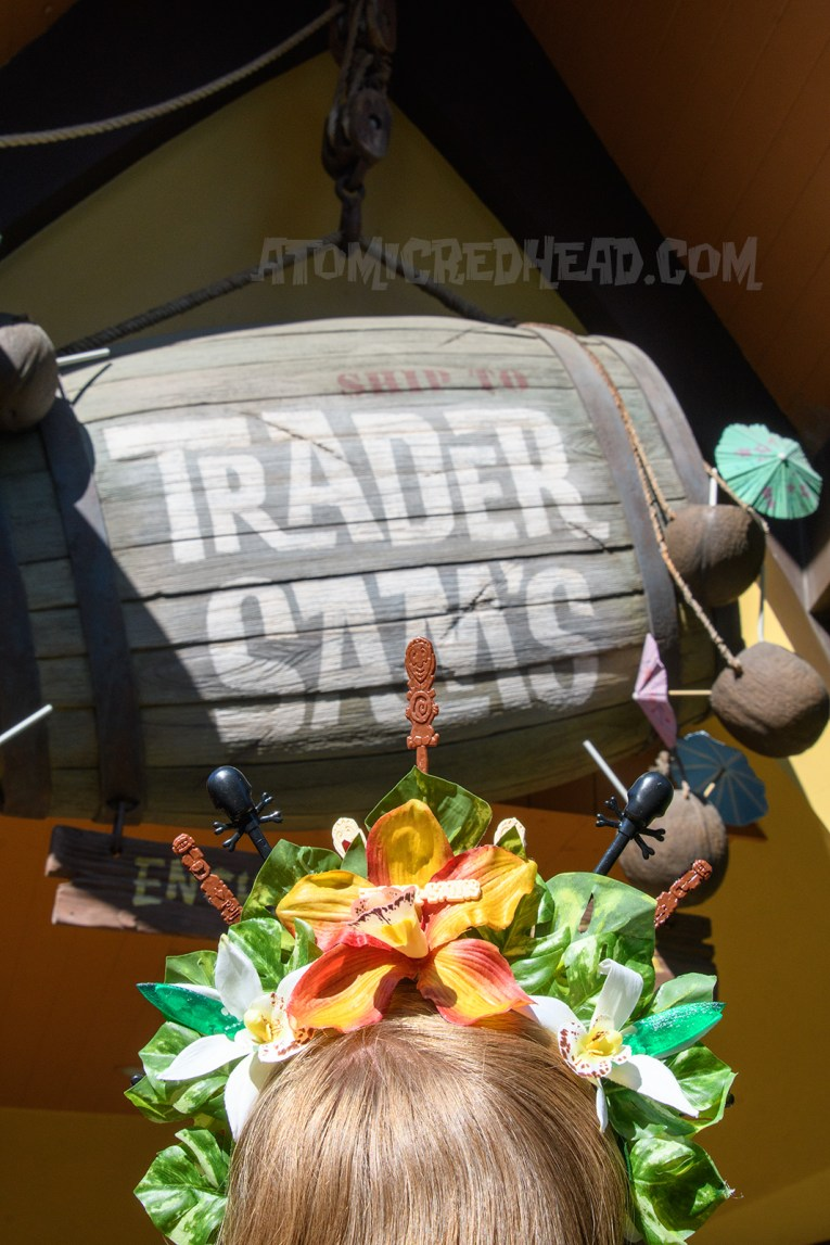 """A barrel reading """"Trader Sam's"""" and the back of my flower crown, featuring orange, red, and white flowers."""