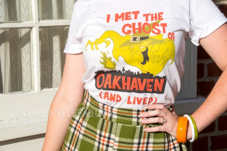 "Close-up of my shirt - a frightening green ghost of a witch rises from the silhouette of a town. Above reads ""I MET THE GHOST OF"" and within the town's silhouette reads ""OAKHAVEN"" and below ""(AND LIVED)"""