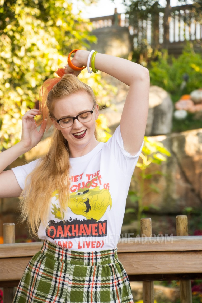 "Myself, standing in front of a small lake with cascading waterfall in the background and pumpkins scattered about, wearing a white t-shirt with an image of a green ghost in a witch hat, rising from a silhouette of a town. Orange text reads ""I met the Ghost of Oakhaven (and lived),"" a skirt in matching green, orange, white and black, and an orange scarf in my pony tail."