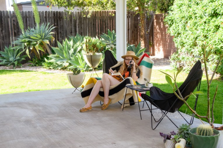 Myself seated in one of our butterfly chairs wearing a black t-shirt featuring a jackalope, reading.