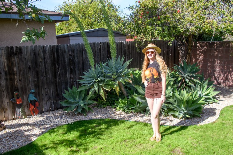 Myself standing in front of the agave plants, wearing a black t-shirt with a jackalope on it, a pair of brown shorts, and a woven straw hat.